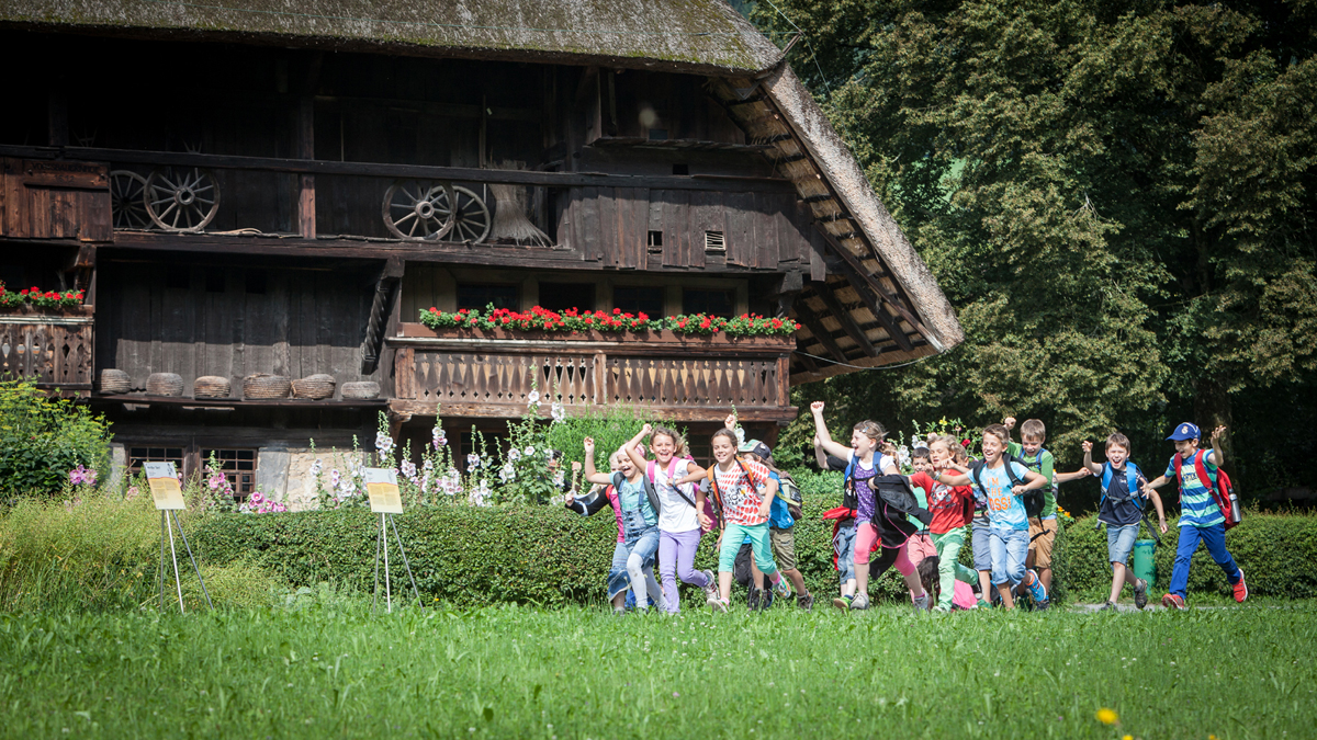 Children running in front of the Vogtsbauernhof