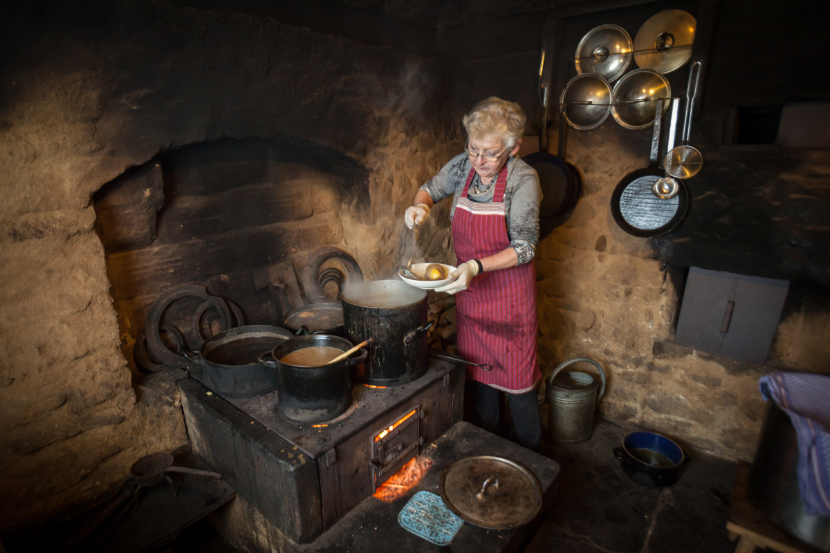 Woman cooking in the black kitchen